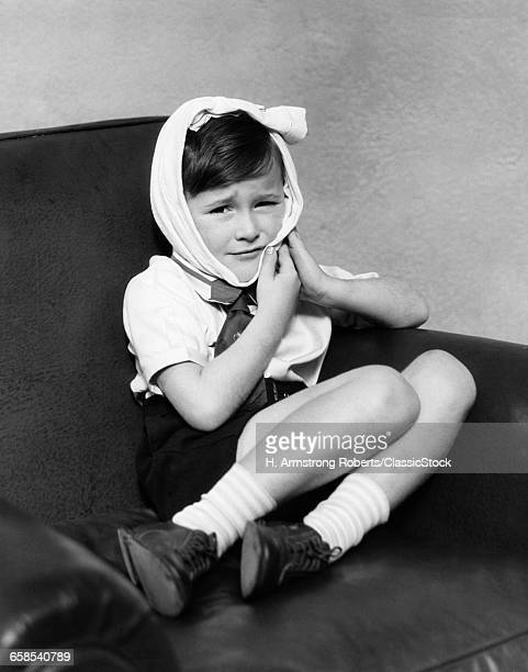 1930s BOY LOOKING AT CAMERA HEAD WRAPPED IN PAIN FROM SORE DENTAL TOOTH ACHE OR FROM MUMPS
