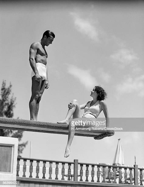 1930s COUPLE ON SWIMMING POOL DIVING BOARD TALKING