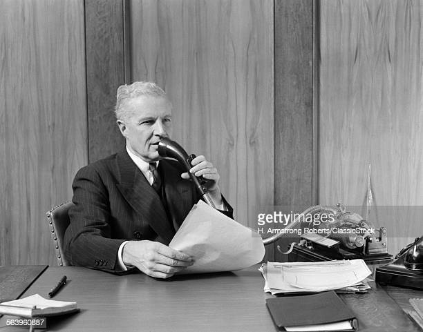 1930s ELDERLY MALE EXECUTIVE SITTING AT DESK SPEAKING INTO DICTAPHONE