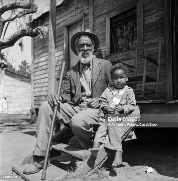 1930s ELDERLY MAN GRANDFATHER SIT PORCH SHACK WITH GRANDSON BOY LOOKING AT CAMERA