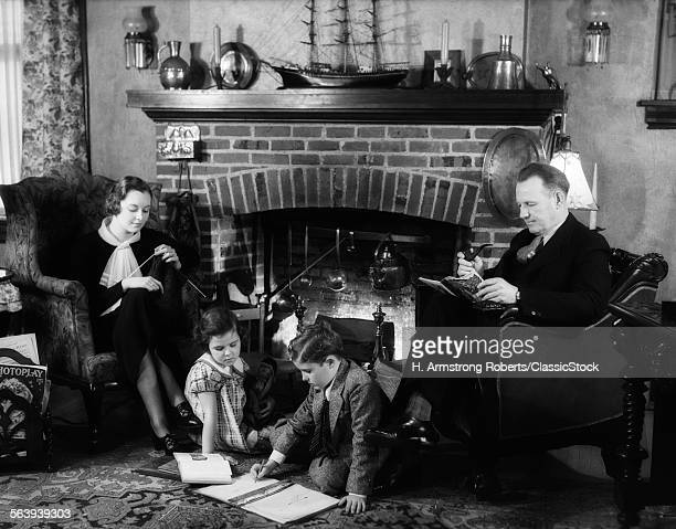 1930s FAMILY OF FOUR SITTING IN FRONT FIREPLACE MOTHER KNITTING FATHER READING SMOKING PIPE KIDS DOING HOMEWORK
