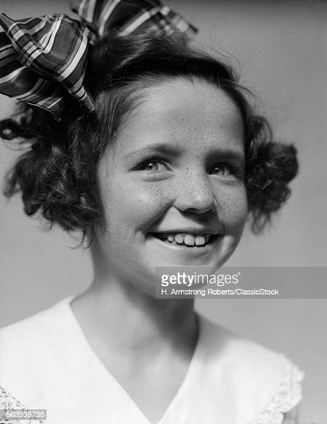 1930s FRECKLE FACED SMILING GIRL WITH BIG RIBBON BOW IN HAIR LOOKING AT CAMERA