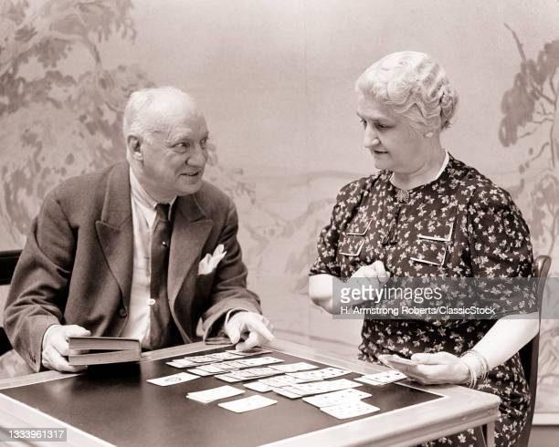 1930s Funny Senior Retired Man And Woman Indignant Wife Playing Solitaire Card Game Husband Kibitzing With Helpful Suggestions .