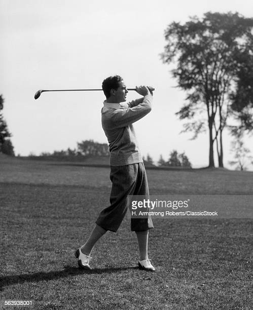 1930s GOLFER IN KNICKERS WITH CLUB IN AIR