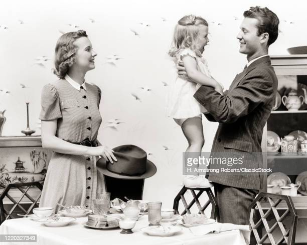 1930s happy family after eating breakfast dad about to leave for work lifting laughing daughter smiling mom holding his hat