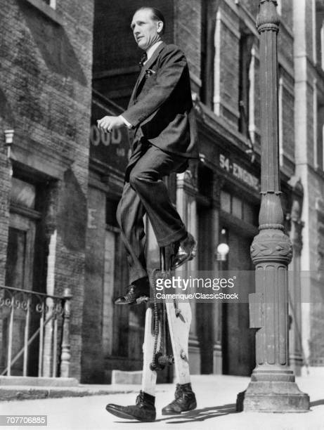 1930s INVENTOR WALTER NILSSON SITTING ON UNICYCLE WHILE WALKING TO WORK ON STILTS LOS ANGELES USA