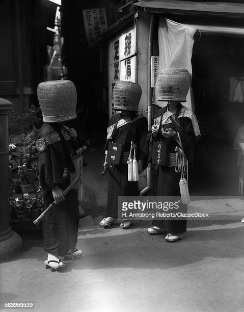 1930s JAPANESE MENDICANT HOLY MEN IN FRONT OF RELIGIOUS TEMPLE WEARING BASKETS OVER HEADS FORM OF ZEN BUDDHISM