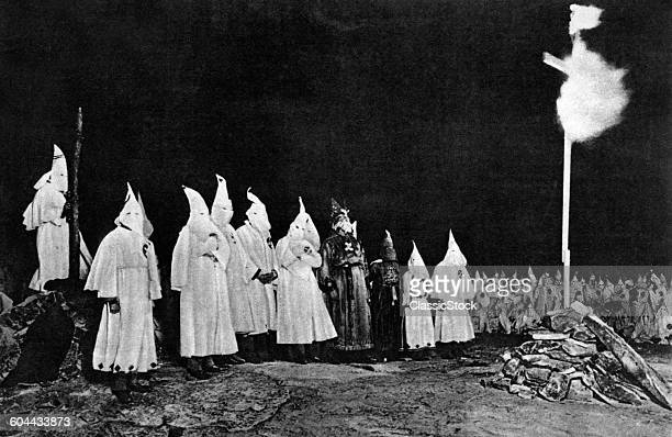 1930s KU KLUX KLAN GATHERING WITH IMPERIAL WIZARD OPPOSITE BURNING CROSS IN RURAL GEORGIA USA