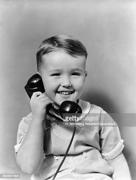 1930s LITTLE BOY SMILING TALKING ON TELEPHONE