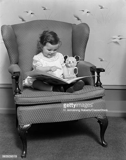 1930s LITTLE GIRL CHILD IN LARGE CHAIR WITH BEAR READING BOOK