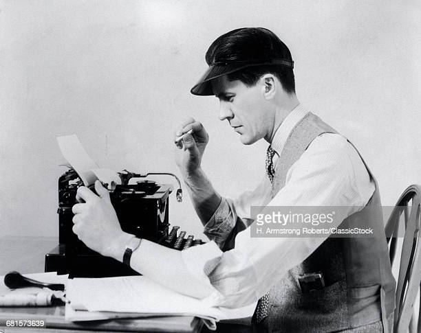 1930s MAN AT THE TYPEWRITER WEARING A VISOR SHIRT TIE AND VEST SMOKING A CIGARETTE WHILE TAKING PAPER FROM THE TYPEWRITER