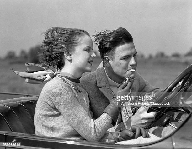 1930s MAN DRIVING CONVERTIBLE AUTOMOBILE WHILE GIRLFRIEND LIGHTS HIS CIGARETTE