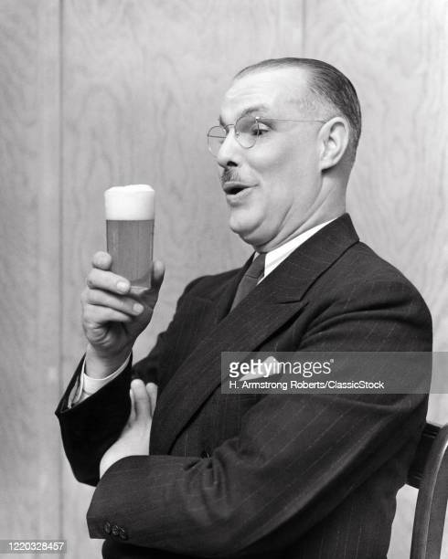1930s man in profile wearing pinstripe suit admiring the foam on a glass of beer