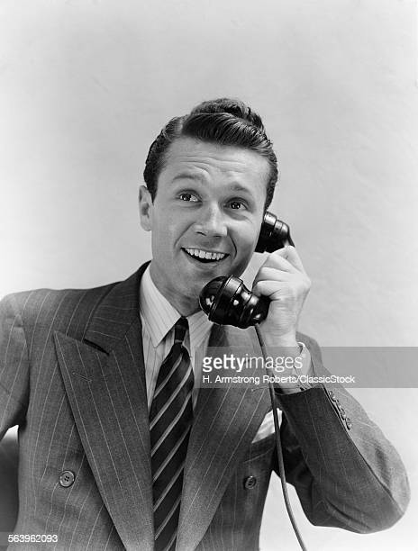 1930s MAN IN SUIT TALKING ON TELEPHONE