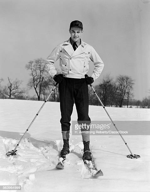1930s MAN LOOKING AT CAMERA POSING IN SKIS HOLDING SKI POLES ON SNOW