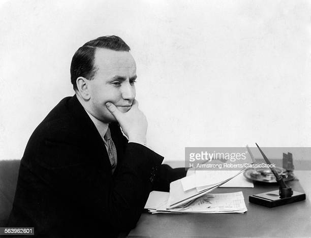 1930s MAN SITTING AT DESK HOLDING PAPERS WITH CONCERNED LOOK ON FACE