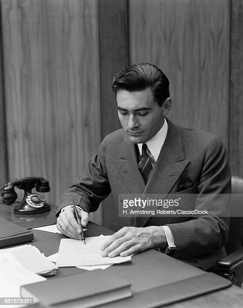 1930s MAN SITTING AT DESK IN OFFICE WRITING