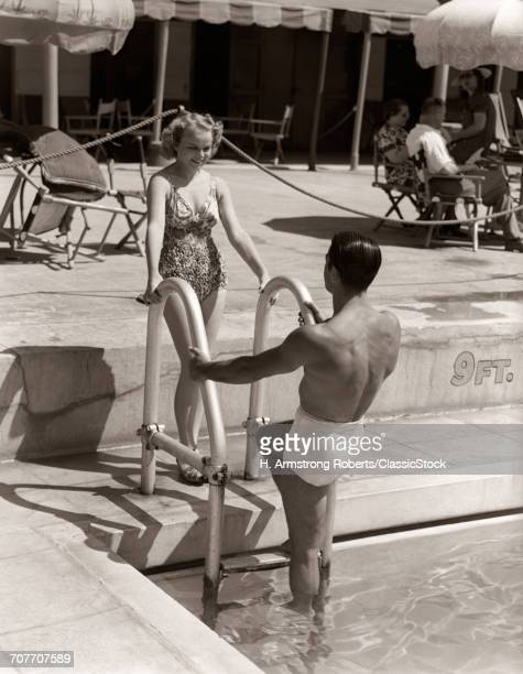 1930s MAN WOMAN COUPLE IN BATHING SUITS POOL SIDE VACATION HOTEL MIAMI BEACH FLORIDA USA