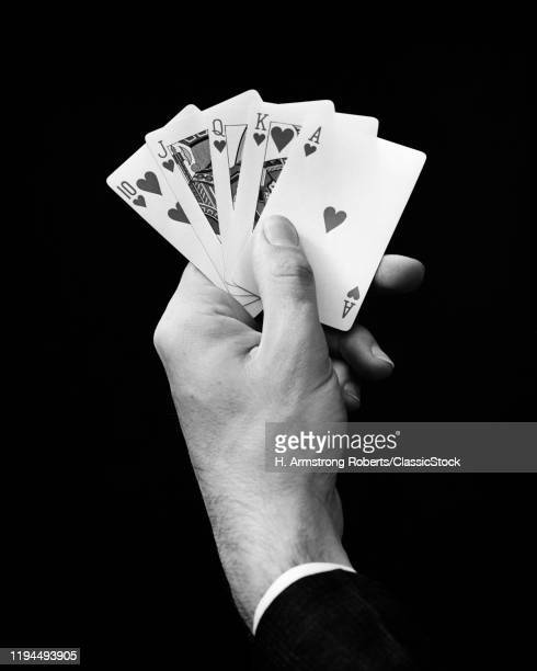1930s MAN'S HAND HOLDING 5 PLAYING CARDS A POKER HAND THAT IS A ROYAL STRAIGHT FLUSH IN HEARTS