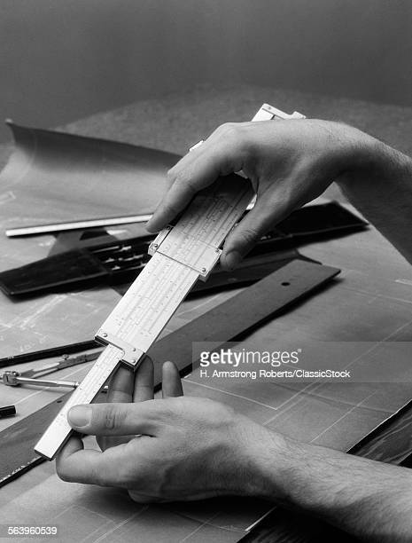 1930s MAN'S HANDS USING SLIDE RULE OVER DRAFTING TABLE
