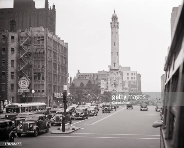 1930s MICHIGAN AVENUE TRAFFIC IN CHICAGO ILLINOIS IN BACKGROUND THE OLD WATER TOWER SURVIVOR OF THE 1871 GREAT FIRE