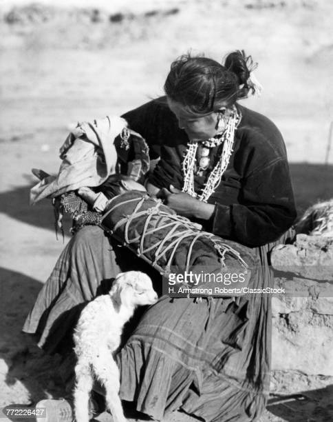 1930s NATIVE AMERICAN NAVAJO WOMAN MOTHER BREAST FEEDING BABY IN PAPOOSE BABY LAMB AT HER FEET