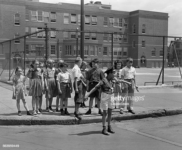 1930s PATERSON NJ BOY CROSSING GUARD HOLDING BACK GROUP OF ELEMENTARY SCHOOL STUDENTS WAITING AT CURB TO CROSS STREET