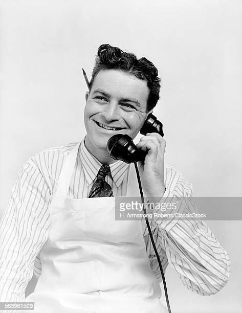 1930s PORTRAIT SMILING MAN CLERK WEARING APRON TALKING ON TELEPHONE PENCIL BEHIND EAR