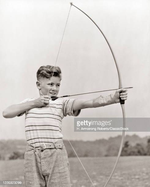 1930s preteen boy aiming bow and arrow