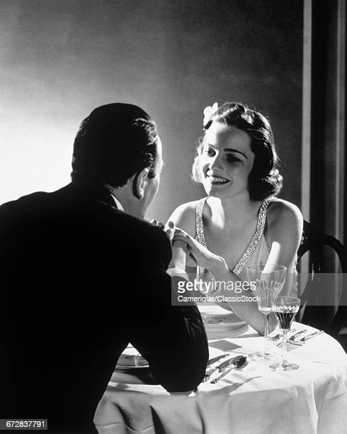 1930s ROMANTIC COUPLE MAN AND WOMAN HOLDING HANDS SEATED AT AN ELEGANT DINNER TABLE