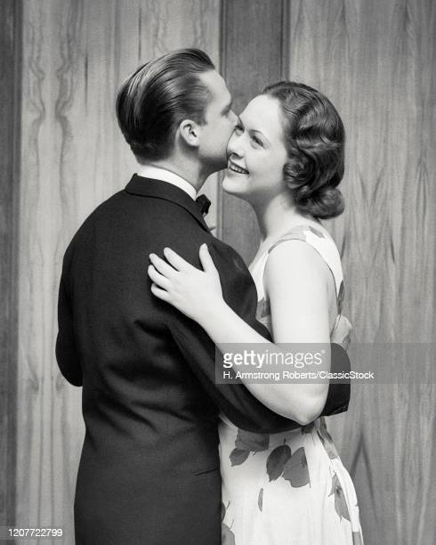 1930s romantic couple wearing formal evening clothes in an embrace dancing back view of man woman smiling.
