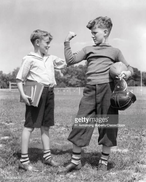 1930s schoolboy feeling arm muscle bicep of his older stronger football player brother