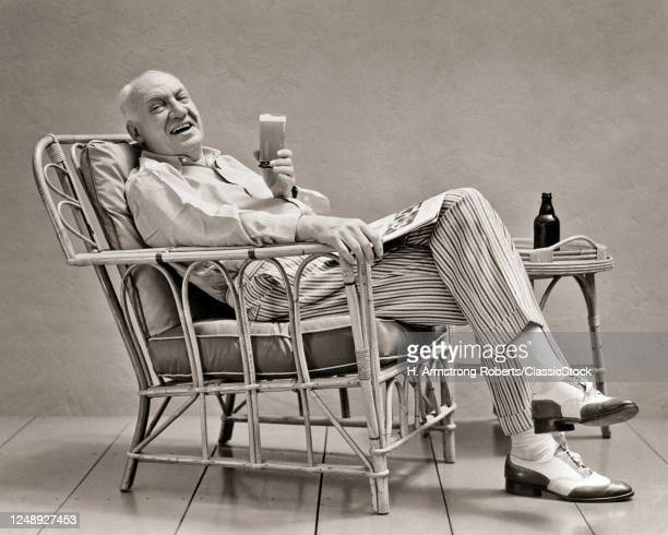 1930s Senior Man In Striped Trousers Spectator Shoes Relaxing In Rattan Chair Reading Magazine Drinking Beer Looking At Camera