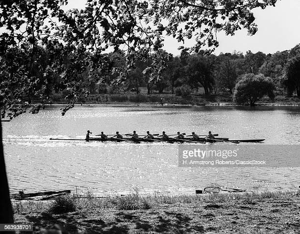 1930s SILHOUETTE SCULLING BOAT RACE ON THE SCHUYLKILL RIVER BETWEEN EAST AND WEST RIVER DRIVES PHILADELPHIA PA USA