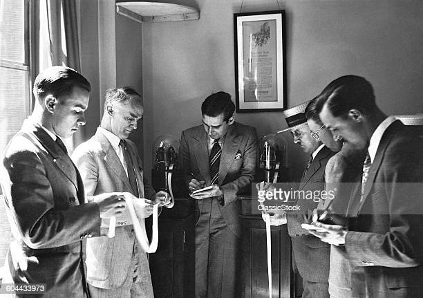 1930s SIX ENGROSSED INVESTORS AND STOCK BROKERS READING PAPER TICKER TAPE INVENTED IN 1867 BY EDWARD CALLAHAN NEW YORK CITY USA