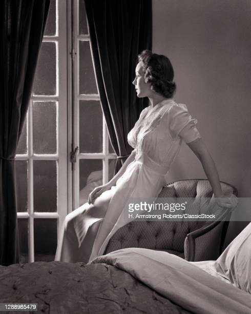 1930s Sleepless Woman Looking Out Of Bedroom Window Leaning On Chair Wearing Negligee
