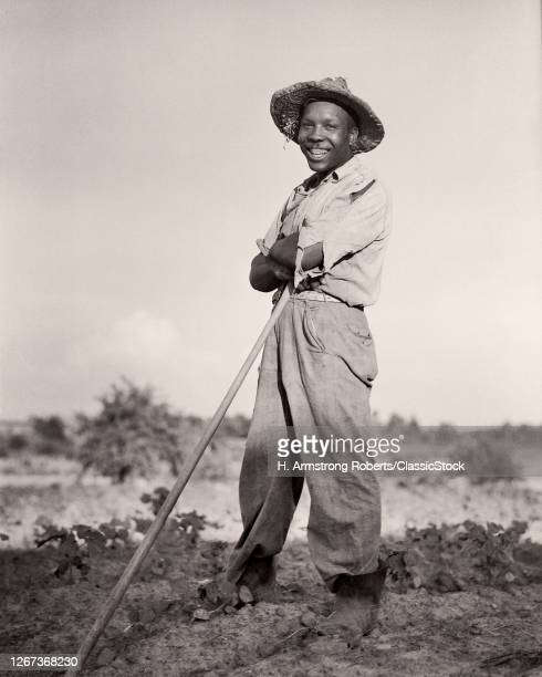 1930s Smiling African-American Man Tobacco Farmer Wearing Straw Hat Standing Leaning On Hoe Looking At Camera North Carolina USA