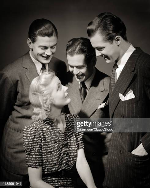 1930s SMILING ATTRACTIVE BLOND WOMAN SURROUNDED BY THREE ATTENTIVE MALE ADMIRERS