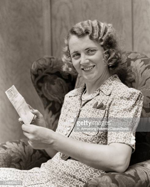 1930s Smiling Blond Woman Sitting In Chair Looking At Camera Holding Reading Showing Western Union Telegram