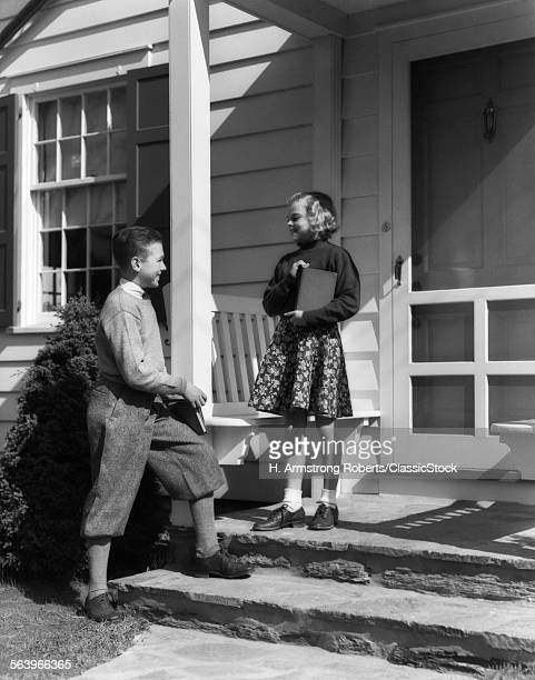1930s SMILING BOY IN KNICKERBOCKERS HOLDING SCHOOL BOOKS TALKING TO GIRL STANDING ON PORCH OF HOUSE