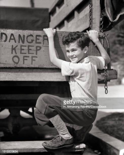 1930s Smiling Boy Looking At Camera Hopping Free Ride On Back Of Moving Truck Sign Reads Danger Keep Off.