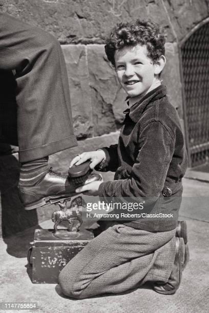 1930s SMILING CAUCASIAN SELFEMPLOYED TEENAGE STREET CORNER SHOESHINE BOY LOOKING AT CAMERA WHILE POLISHING MAN'S SHOE