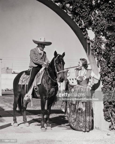 1930s SMILING CAUCASIAN WOMAN IN TRADITIONAL CHINA POBLANA COSTUME TALKING TO MEXICAN MAN HORSEACK WEARING CHARRO COWBOY CLOTHES