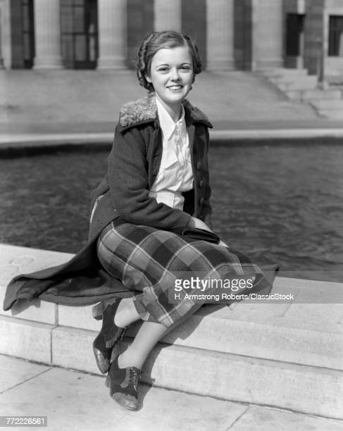 1930s SMILING TEEN GIRL SITTING AUTUMN CLOTHES LOOKING AT CAMERA