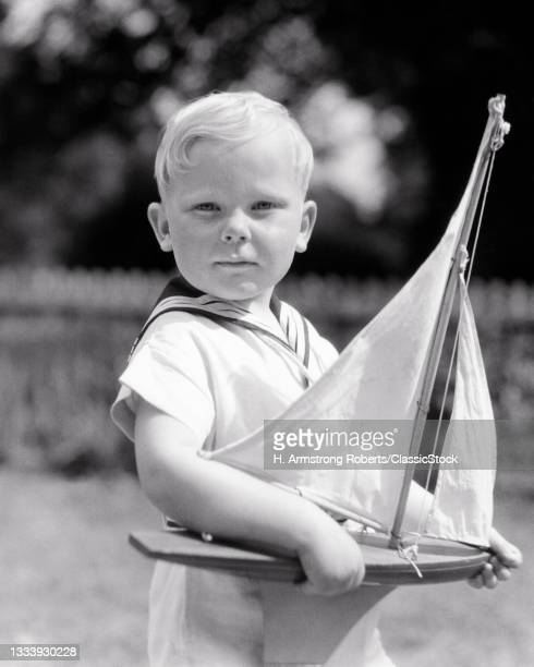 1930s Sun Washed Blonde Boy In Sailor Collar Shirt Holding Toy Sailboat Serious Proud Facial Expression Looking At Camera .
