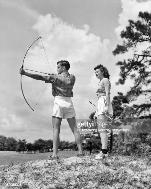 1930s TEENAGE COUPLE PRACTICING ARCHERY SHOOTING BOW AND ARROW