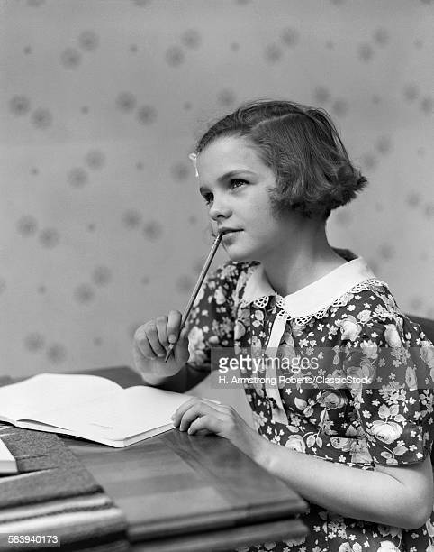 1930s TEENAGE GIRL THINKING SITTING AT TABLE DOING HOMEWORK