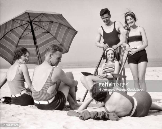 1930s THREE COUPLES SMILING MEN AND WOMEN WEARING BATHING SUITS GATHERED STANDING SITTING LYING TOGETHER ON BEACH AT SEASHORE