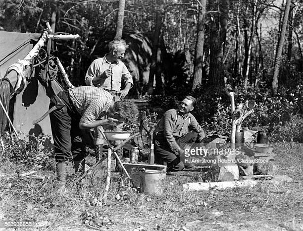 1930s THREE MEN AT CAMPSITE ONE WASHING HIS FACE AT WASH STAND THE OTHER TENDING CAMPFIRE LAKE OF THE WOODS ONTARIO CANADA
