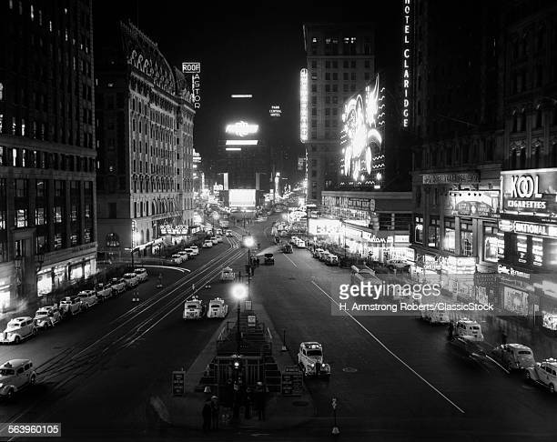 1930s OVERHEAD OF TIMES SQUARE LIT UP AT NIGHT WITH CARS LINING CURBS NYC NY USA